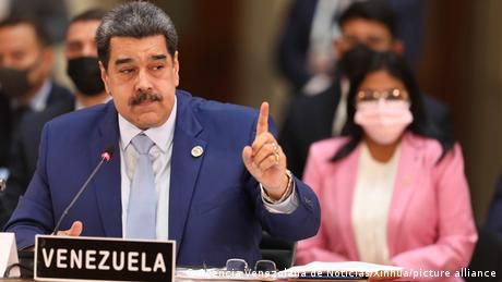 Maduro raises his figure, as he sits at summit desk