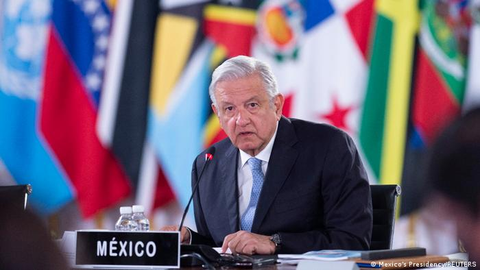 Andres Manuel Lopez Obrador sitting at microphone at summit