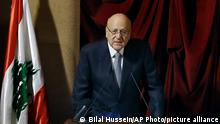 Lebanese Prime Minister Najib Mikati speaks during a parliament session to confirm Lebanon's new government at a Beirut theater known as the UNESCO palace so that parliament members could observe social distancing measures imposed over the coronavirus pandemic, Lebanon, Monday, Sept. 20, 2021. A power outage and a broken generator briefly delayed the start of the parliament session for some 40 minutes before electricity came back on. (AP Photo/Bilal Hussein)