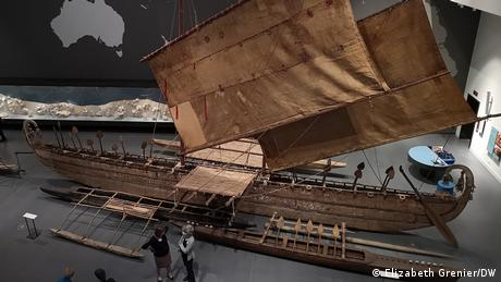 Two people stand next to a huge ancient sailing ship at the Humboldt Forum museum.