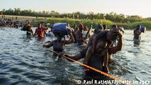 Foto simbólica de personas migrantes de Haití que cruzan un río entre México y Estados Unidos.