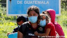 Central American migrants stand at the Mexico - Guatemala border after they were expelled by U.S. and Mexican officials, in El Ceibo, Guatemala August 15, 2021. The sign reads Limit of the Republic of Guatemala. Picture taken August 15, 2021. REUTERS/Luis Echeverria