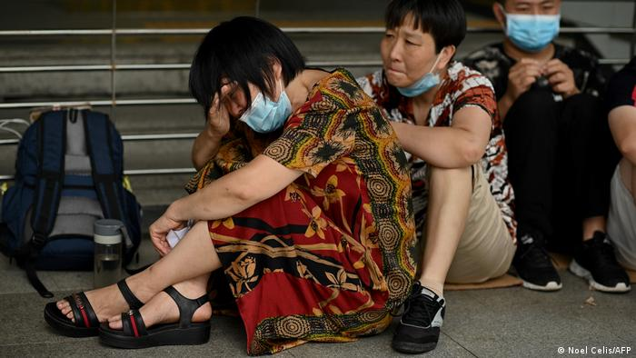 Una mujer llora mientras ella y otras personas se reúnen en la sede de Evergrande en Shenzhen, sureste de China, ya que el gigante inmobiliario chino dijo que enfrenta dificultades sin precedentes, pero negó los rumores de que está a punto de hundirse.