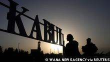 FILE PHOTO: Taliban soldiers stand in front of a sign at the international airport in Kabul, Afghanistan, September 9, 2021. WANA (West Asia News Agency) via REUTERS ATTENTION EDITORS - THIS IMAGE HAS BEEN SUPPLIED BY A THIRD PARTY./File Photo