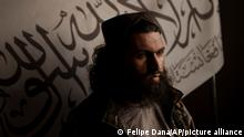 Taliban district police chief Shirullah Badri stands in front of a Taliban flag during an interview at his office in Kabul, Afghanistan, Monday, Sept. 20, 2021. (AP Photo/Felipe Dana)