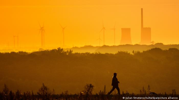 A man walks with a coal plant and a wind farm in the background