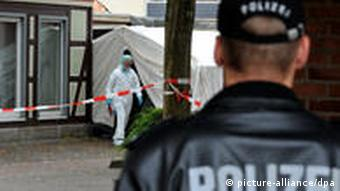 A German police officer stands with his back to the camera, observing a crime scene
