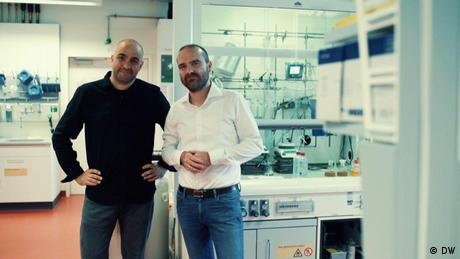 Two men stand in a laboratory