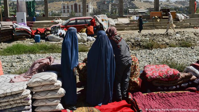 A vendor shows items for sale to Burqa-clad women at a temporary second-hand market in Kabul, Afghanistan