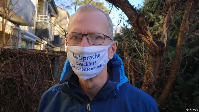 Stefan Palm-Ziesenitz, Chairperson of the Hamburg's Association for the Dear, outside in front of a tree, wearing a mask that says spoken language is pointless; please use sign language.