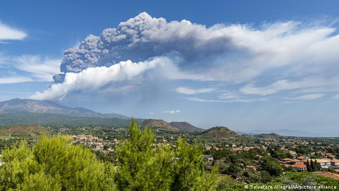 Mount Etna erupts in the background of this photo, which shows bucolic homes in Italy