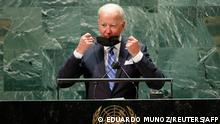 US President Joe Biden takes off his protective facemask due to the coronavirus disease (Covid-19) pandemic as he arrives to speak at the 76th Session of the UN General Assembly on September 21, 2021 in New York. - The summit will feature the first speech to the world body by US President Joe Biden, who has described a rising and authoritarian China as the paramount challenge of the 21st century. (Photo by EDUARDO MUNOZ / POOL / AFP)