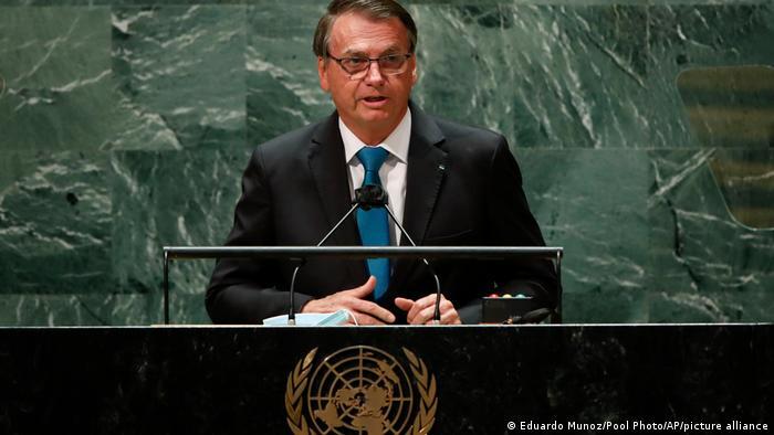 Bolsonaro fala em um púlpito. Ele veste terno escuro e usa óculos.