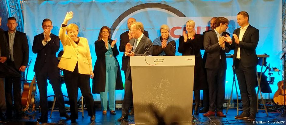Chancellor Angela Merkel (waving) and chancellor candidate Armin Laschet (behind podium) at a campaign event in Stralsund, Germany on September 21, 2021
