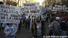 People march during a demonstration called by social organizations to protest against the government of Argentina's President Alberto Fernandez, towards Plaza de Mayo square and the Casa Rosada Presidential Palace in Buenos Aires on September 21, 2021. - The demonstrators are demanding genuine jobs, basic salaries of $70,000 (some 675 US dollars) and the resignation of the antiabortion Argentine chief cabinet Juan Manzur. Fernandez reshuffled his cabinet to smother a political crisis that pitted him bitterly against his vice president this week after an electoral defeat in legislative primaries. (Photo by Juan MABROMATA / AFP)