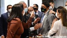 Tebet, de blusa marrom, aponta o dedo para Wager Rosário, Há muitas pessoas ao redor. Todos usam máscara.