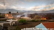 Houses amid smoke and flames with the volcano in the background
