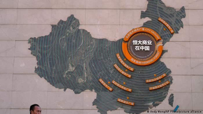 A custodian stands near a map showing Evergrande development projects in China on a wall in an Evergrande city plaza in Beijing