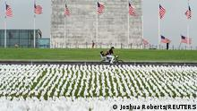 A cyclist rides past an exhibition of white flags representing Americans who have died of coronavirus disease (COVID-19), placed over 20 acres of the National Mall, in Washington, U.S., September 17, 2021. REUTERS/Joshua Roberts TPX IMAGES OF THE DAY