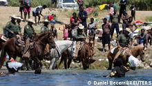 U.S. Border Patrol agents sit on horses near the banks of the Rio Grande river, border between Ciudad Acuna, Mexico and Del Rio, Texas, U.S., as migrants seeking refuge into the United States cross the river, in Ciudad Acuna, Mexico September 20, 2021. REUTERS/Daniel Becerril
