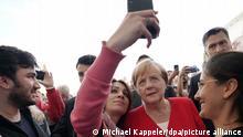 Bundeskanzlerin Angela Merkel (CDU) lässt sich während des Tages der offenen Tür der Bundesregierung im Ehrenhof des Bundeskanzleramtes mit Besuchern fotografieren. +++ dpa-Bildfunk +++