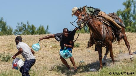 A United States Border Patrol agent on horseback tries to stop a Haitian migrant from entering an encampment on the banks of the Rio Grande, Texas