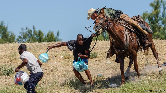 Guarda americano em cima de um cavalo puxa pela camisa um migrante que corre com sacolas na mão, nas margens do Rio Grande, na fronteira dos EUA com o México