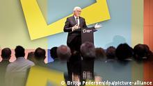 Steinmeier fala em um palco, atrás de um púlpito, Há muitas pessoas na plateia.