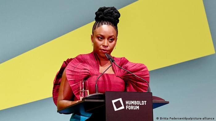 Chimamanda Ngozi Adichie wearing a ruffled red dress and standing at the podium.
