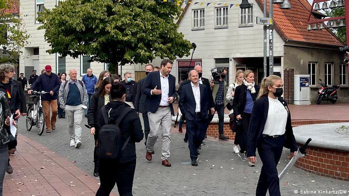 Lars Klingbeil (center left) walks with Scholz through a small town