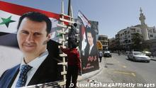 Men hang the national flag next to posters of President Bashar al-Assad, a candidate for the Presidential election, in the Syrian capital Damascus on May 17, 2021. - A Syrian former minister and a member of the Damascus-tolerated opposition will face Bashar al-Assad in this month's presidential election, the constitutional court said. The Assad-appointed body approved only three out of 51 applications to stand in the May 26 ballot, among them the 55-year-old president himself, widely expected to win a fourth mandate. (Photo by LOUAI BESHARA / AFP) (Photo by LOUAI BESHARA/AFP via Getty Images)
