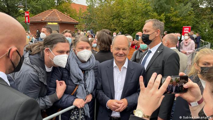 Olaf Scholz at a campaign event with his supporters and security personnel