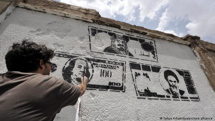 A mural depicting US, Saudi and Iranian currency banknotes as a comment against foreign interference in Yemen.