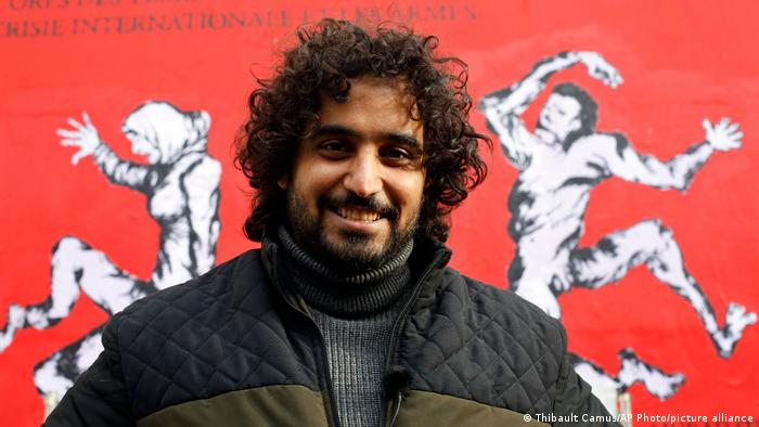 Murad Subay, a smiling man, stands in front of a painting showing black-and-white distorted figures on a red background.