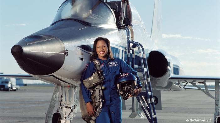 A woman leans against a plane wearing a blue NASA jumpsuit and cradling her helmet