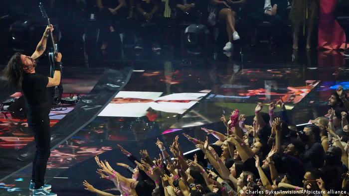 Dave Grohl steht mit Gitarre auf der Bühne, vor ihm im Publikum strecken die Leute die Hände nach ihm aus