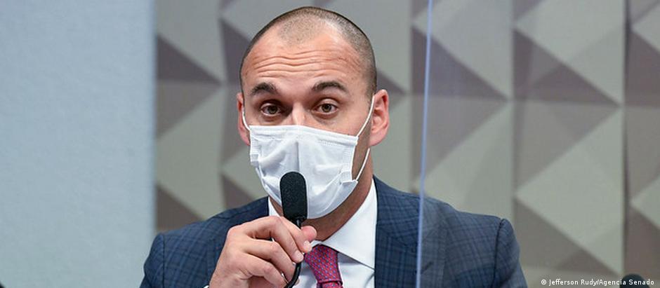 Batista está sentado atrás de um microfone. Ele está de máscara.