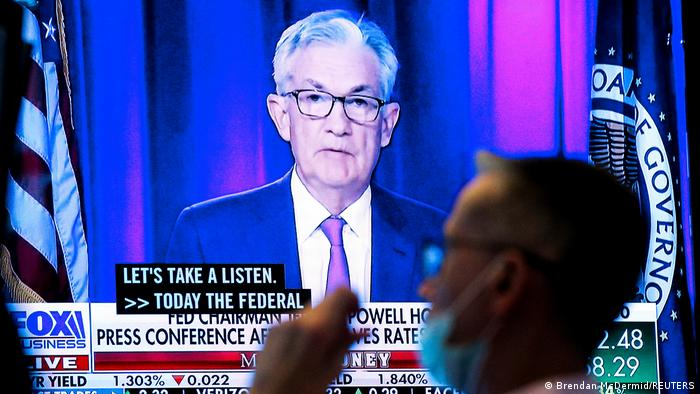 A photo of Jerome Powell on a TV screen with a scholarship staring at him