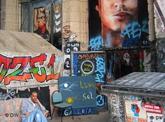 A man sits in the court at Tacheles surrounded by graffiti art
