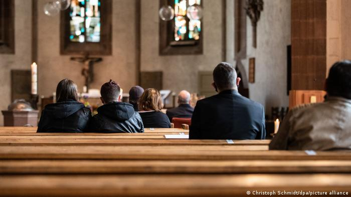 A handful of people sit int the pews of a church