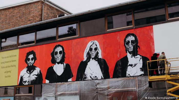 Artists painting a mural showing black-and-white portraits, people with skeletal faces and black holes instead of eyes, on a red background.