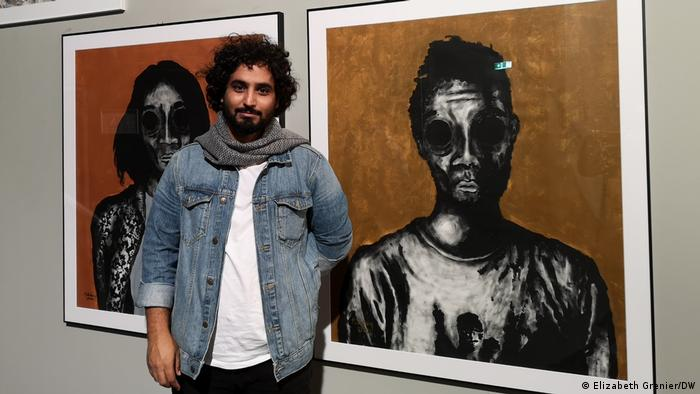Artist Murad Subay stands in front of two of his paintings.