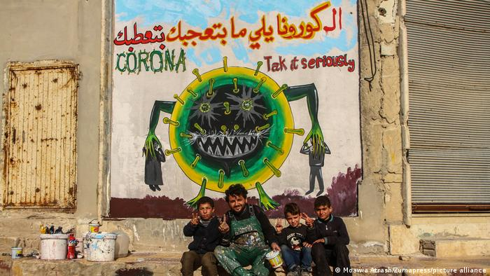 Syrian artist Aziz al Asmar seated with children in front of one of his murals.