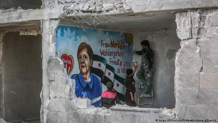 Man standing on a ladder painting a wall of a destroyed building. He is assisted by another man and watched by a boy.
