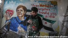 A man in overalls mixes paint in fron of a mural featuring a woman and the Syrian flag