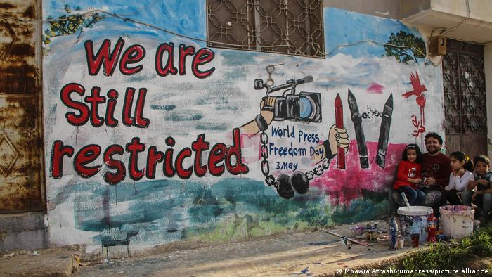 Man paints a mural on a wall with the words We are still restricted.