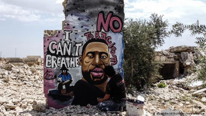 A man paints a portrait of a Black man on a wall that stands amid rubble.