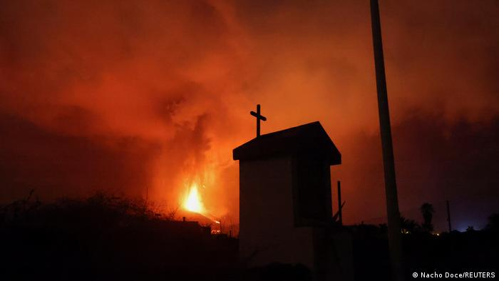 The dark outline of a church is juxtaposed with the bright background of volcanic fire engulfing the area.