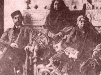 مهد علیا بر روی تخت طاووس (در وسط)، پسرش ناصرالدین شاه و دخترش عزتالدوله
