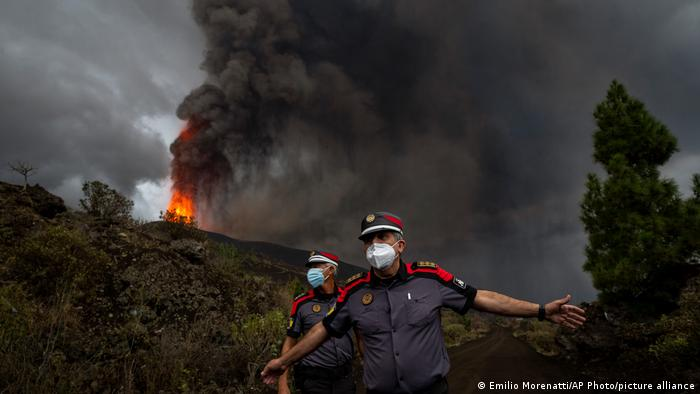 A police officer is pictured against the backdrop of the erupting volcano.
